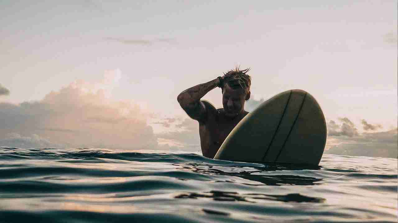 man on a surfboard with right hand on his head